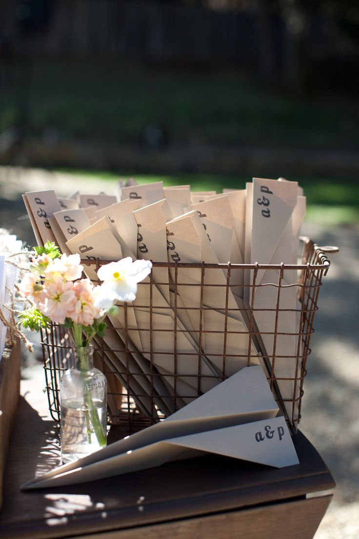 Fold your wedding programs into paper planes for a fun and unexpected touch! Photo via Style Me Pretty