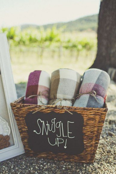 Yet another fun way to make sure guests are warm during chilly fall nights: Have blankets available to guests for use during the ceremony or to keep as wedding favors. Photo  by  Sarah Kathleen Photography  via